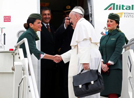 Pope Francis shakes hands with Alitalia's flight attendant in Rome's Leonardo da Vinci-Fiumicino airport as he boarded a plane for his pastoral trip to Egypt yesterday