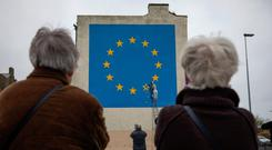 People gather to look at a Banksy mural depicting a European Union flag being chiselled by a workman on the side of a disused building in Dover, England. Photo: Bloomberg