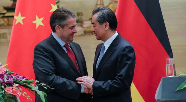 Chinese Foreign Minister Wang Yi (R) shakes hands with German Foreign Minister Sigmar Gabriel at an event in China
