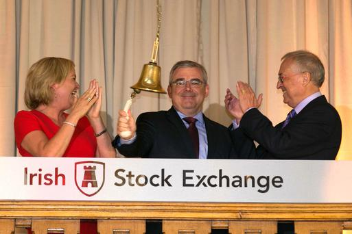 AIB CEO Bernard Byrne rings the bell at the Irish Stock Exchange as Deirdre Somers, CEO of the exchange, and Richard Pym, chairman of AIB, look on