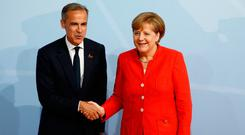 Bank of England governor Mark Carney meeting German Chancellor Angela Merkel in his capacity as the president of the G20's Financial Stability Board at the G20 summit in Hamburg yesterday. Photo: Getty