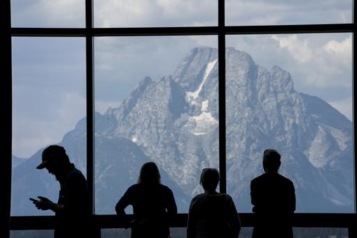 The silhouette of people standing in front of a window in the lobby area of the Jackson Lake Lodge during last year's Jackson Hole economic symposium. Photo: Bloomberg