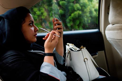 A woman applies make-up while travelling in a taxi cab operated by Uber in Jeddah, Saudi Arabia