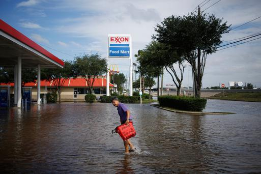 A convenience store owner walks through floodwaters from Hurricane Harvey outside an Exxon Mobil station in Houston