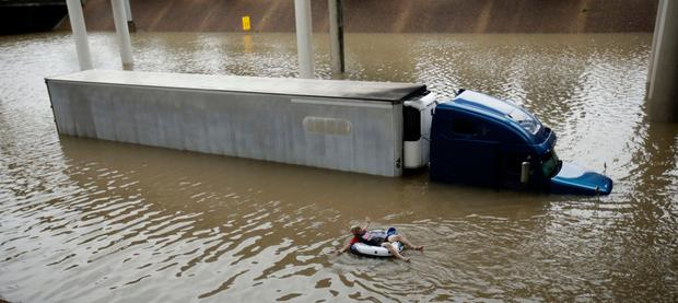 A man floats past a truck submerged on a freeway flooded by Hurricane Harvey near downtown Houston. Photo: AP
