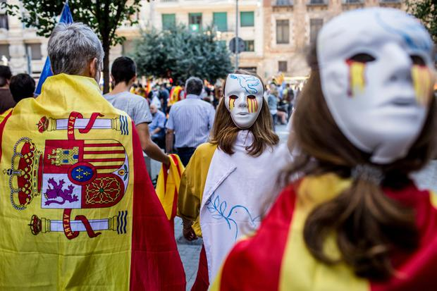 A demonstrator wears a Spanish national flag as others wear masks during a rally in Barcelona supporting Spanish unity Photo: Bloomberg