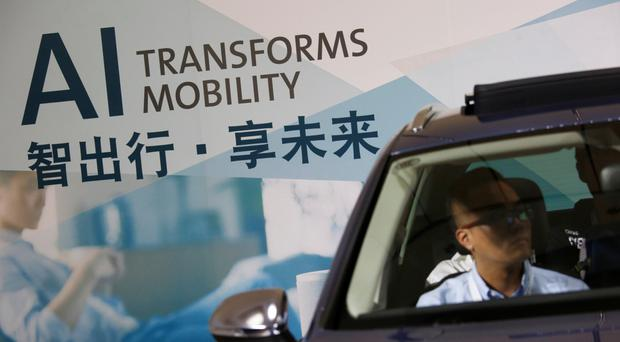 Visitors try out a car at a Volkswagen workshop prior to Auto Guangzhou in Guangzhou