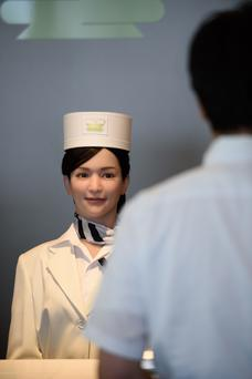 A customer faces a humanoid robot at the reception desk of a hotel in Sasebo, Japan. The restaurant sector is facing especially rapid automation, with consequences for employment. Photo: Bloomberg
