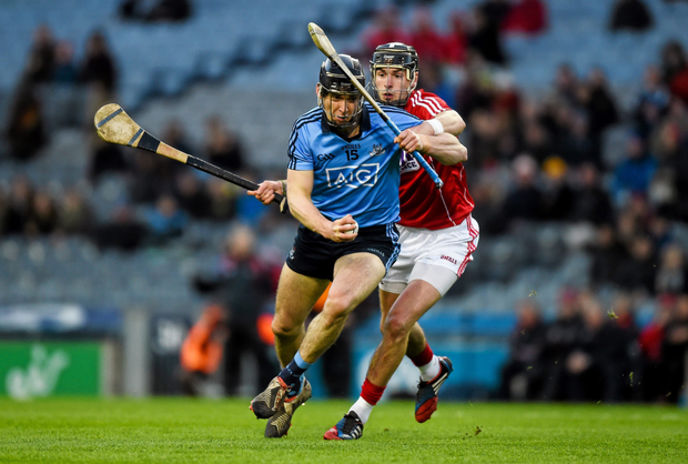 Mark Schutte of Dublin in action against Killian Burke of Cork in the hurling league – a recent study found there were only two hurlers on the Cork panel based outside the county and none in Dublin, but not every county has the jobs and educational infrastructure to keep its young men so close to home. Photo: Ray McManus/Sportsfile