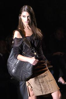A catwalk model displays Gucci designer goods. Tourism is a major factor in the rise in Irish sales
