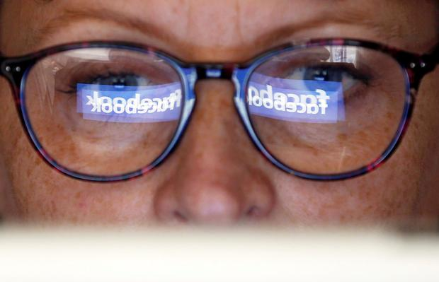The Facebook logo is reflected on a woman's glasses. The company says it had data-sharing partnerships with four Chinese consumer device-makers. Photo: Reuters/Regis Duvignau/Illustrationback