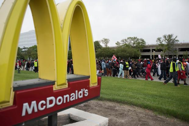 Demonstrators march past a McDonald's restaurant in the US seeking a wage increase. Photo: Bloomberg