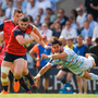 Sam Arnold of Munster, wearing the side's distinctive Adidas kit, is tackled by Maxime Machenaud of Racing 92