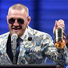 Conor McGregor speaks during a news conference while holding up his Notorious-branded Irish whiskey.