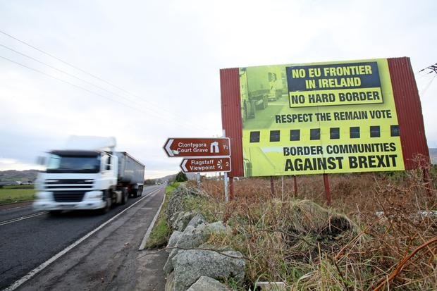 Moving target: Traffic crosses the Border into Northern Ireland from the Republic alongside a Brexit Border poster on the Dublin road between Newry and Dundalk