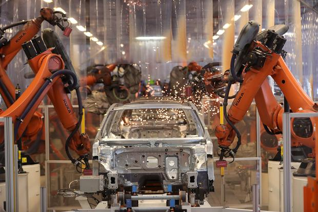 Robotic arms manufactured by Chinese target Kuka operate on a Volkswagen Passat chassis inside the VW factory in Emden, Germany