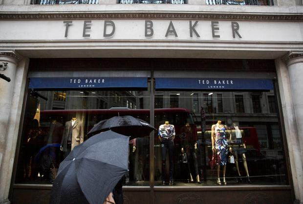 People shelter under umbrellas as they pass a Ted Baker a store in London. Photo: Reuters
