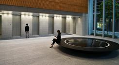 Shire power: A woman sits in the entrance hall of Takeda Pharmaceutical's global HQ in Tokyo, Japan – the company's takeover of Shire is the biggest overseas acquisition by a Japanese company. Photo: Bloomberg