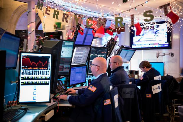 Traders work beneath holiday decorations on the floor of the New York Stock Exchange. Photo: Bloomberg