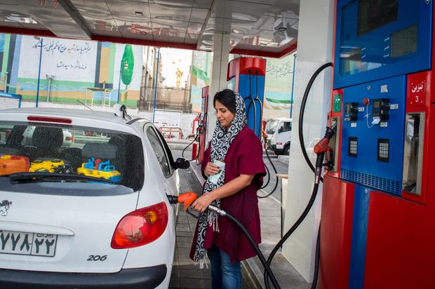 Sanctions: A woman refuels a car at a petrol station in Iran. Photo: Bloomberg