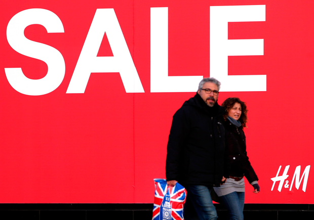 Shoppers pass a sale sign in the window of H&M on Princes Street, Edinburgh. Photo: PA