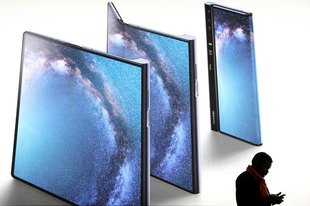 Mate: A man checks his phone next to an advertisement of a new Huawei Mate X device at the Mobile World Congress in Barcelona, Spain