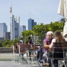 Germany stalling: People sit at a cafe terrace as skyscrapers stand beyond on the city skyline in Frankfurt