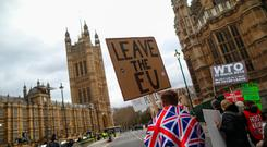 Pro-Brexit campaigners march along the road near the Houses of Parliament on Wednesday, March 13