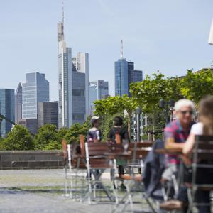 People sit at a cafe terrace as skyscrapers stand beyond on the city skyline in Frankfurt