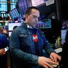 Dressing down: Traders, many in jeans, work on the floor of the New York Stock Exchange on the day that Levi Strauss returned to the stock market. Photo: Getty