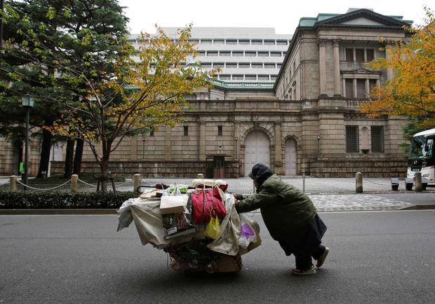 Contrasting fortunes: A homeless man pushes a cart loaded with his belongings outside the Bank of Japan headquarters in Tokyo. Photo: Reuters