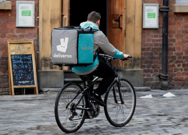 Delivering results: Deliveroo rider carrying a box with its kangaroo logo