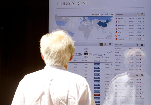 Shared interest: A man looks at a display showing the current stock prices at an office of Swiss bank UBS in Zurich. Photo: REUTERS