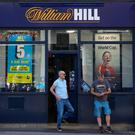 Customers outside the Ludgate Hill, central London branch of William Hill. Photo: PA
