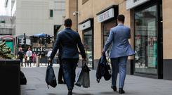 Suited and booted: Traders carry their personal effects as they leave the London offices of Deutsche Bank