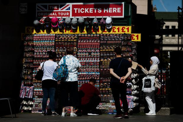 Setting out its stall: Tourists browse discount souvenirs in Trafalgar Square as UK consumer confidence slumps. Photo: Bloomberg
