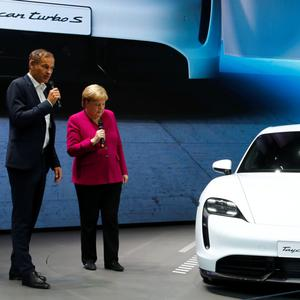 Porsche CEO Oliver Blume and German Chancellor Angela Merkel speak next to the Porsche Taycan Turbo S at the international Frankfurt Motor Show last week. Photo: REUTERS/Ralph Orlowski