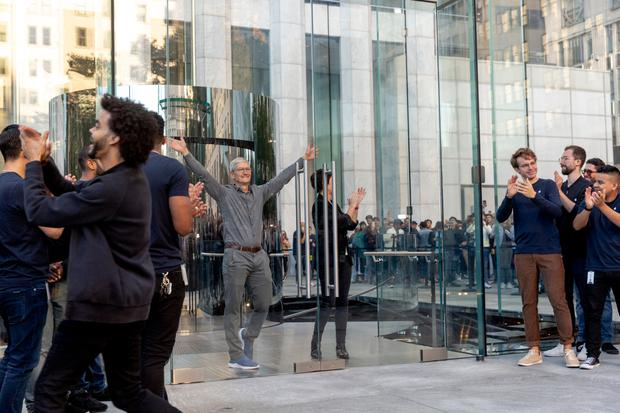 Company CEO Tim Cook waves to customers outside the newly redesigned Apple store on Fifth Avenue, New York. Photo: Bloomberg