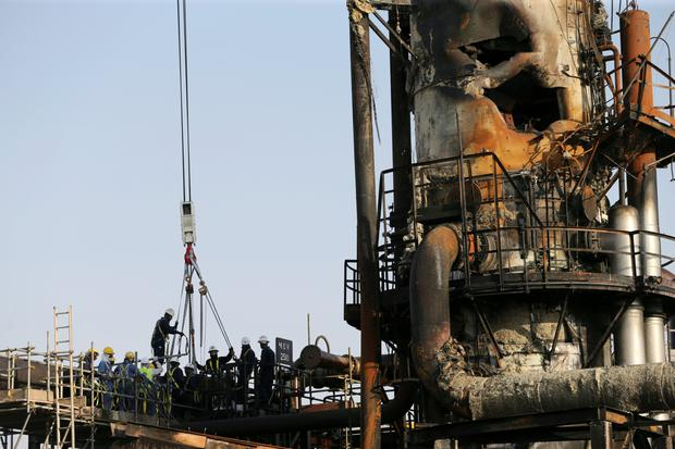 Crippled: Workers at the damaged Abqaiq oil facility in Saudi Arabia