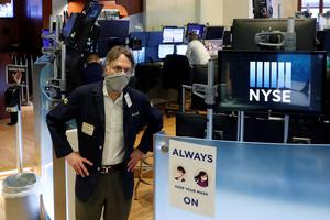 Taking stock: Traders wear masks as they work on the floor of the New York Stock Exchange. Photo: REUTERS