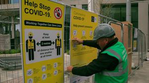 Back to work: Compliance officer John Gaskin puts up Covid-19 social distancing signs on a building site in Dublin city centre during lockdown. PHOTO: GARETH CHANEY/COLLINS