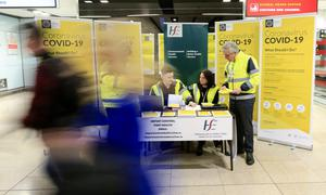 Passengers in Dublin Airport pass by a Covid-19 information stand. Photo: Gerry Mooney