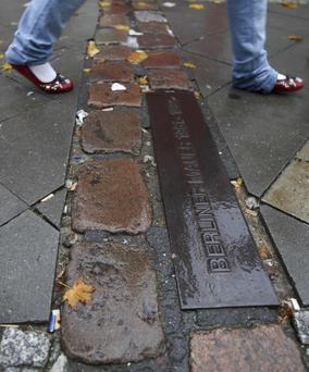 A woman walks over a wall marking next to the former Berlin Wall border checkpoint, Checkpoint Charlie in Berlin