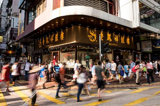 Pedestrians cross a road in front of a Lao Feng Xiang Co. jewelry store in the Mong Kok district of Hong Kong,