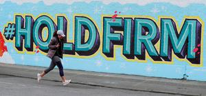 Resolve: A woman runs past a mural in Dublin city centre at the height of the Covid lockdown Photo: Brian Lawless / PA Wire