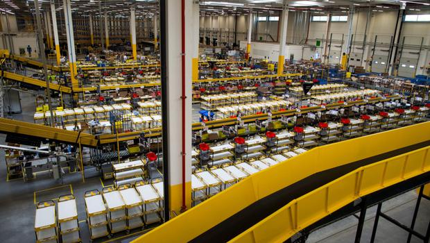 Conveyor belts pass through the product packaging system inside the new Amazon Inc. fulfilment center on its official day of opening in Bielany Wroclawskie, Poland, on Tuesday, Oct. 28, 2014. The company announced on Monday that it's taking preorders for a streaming media stick that plugs into a TV, making it possible to watch a range of Internet video services. Photographer: Bartek Sadowski/Bloomberg