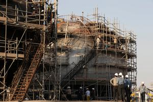 Attack: Workers attempt repairs on the damaged refinery site in Abqaiq, Saudi Arabia. Photo: Bloomberg