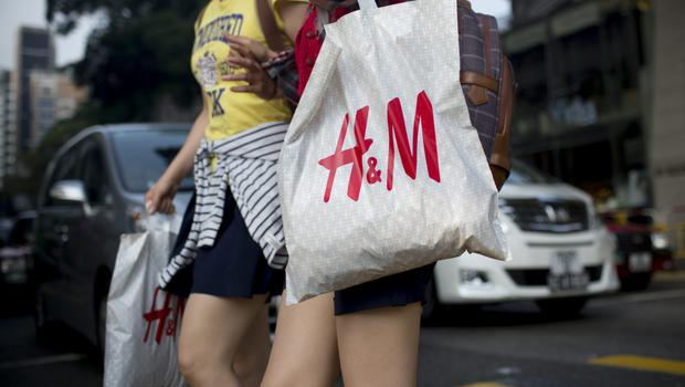Pedestrians carrying Hennes & Mauritz AB (H&M) shopping bags cross Canton Road in the Tsim Sha Tsui area of Hong Kong, China, on Wednesday Credit: Brent Lewin/Bloomberg