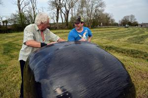 19/04/2020  Jarlath Farrell and Damien McGrath chat over a silage bail, as Damien's land is cut for the first time this year.  Photo: Ray Ryan