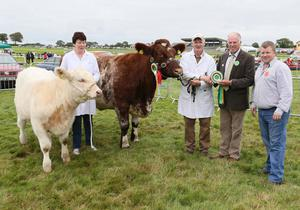 Nora and Noel O'Dowd, Creggs, Co Galway, who won the Overall Champion with their Shorthorn Cow in the Cattle section at Ballinrobe Agricultural Show, are presented with rosette by Seamus Macken, Show chairman, alongside judge Niall Faughnan, Mohill. Photo: Michael Donnelly
